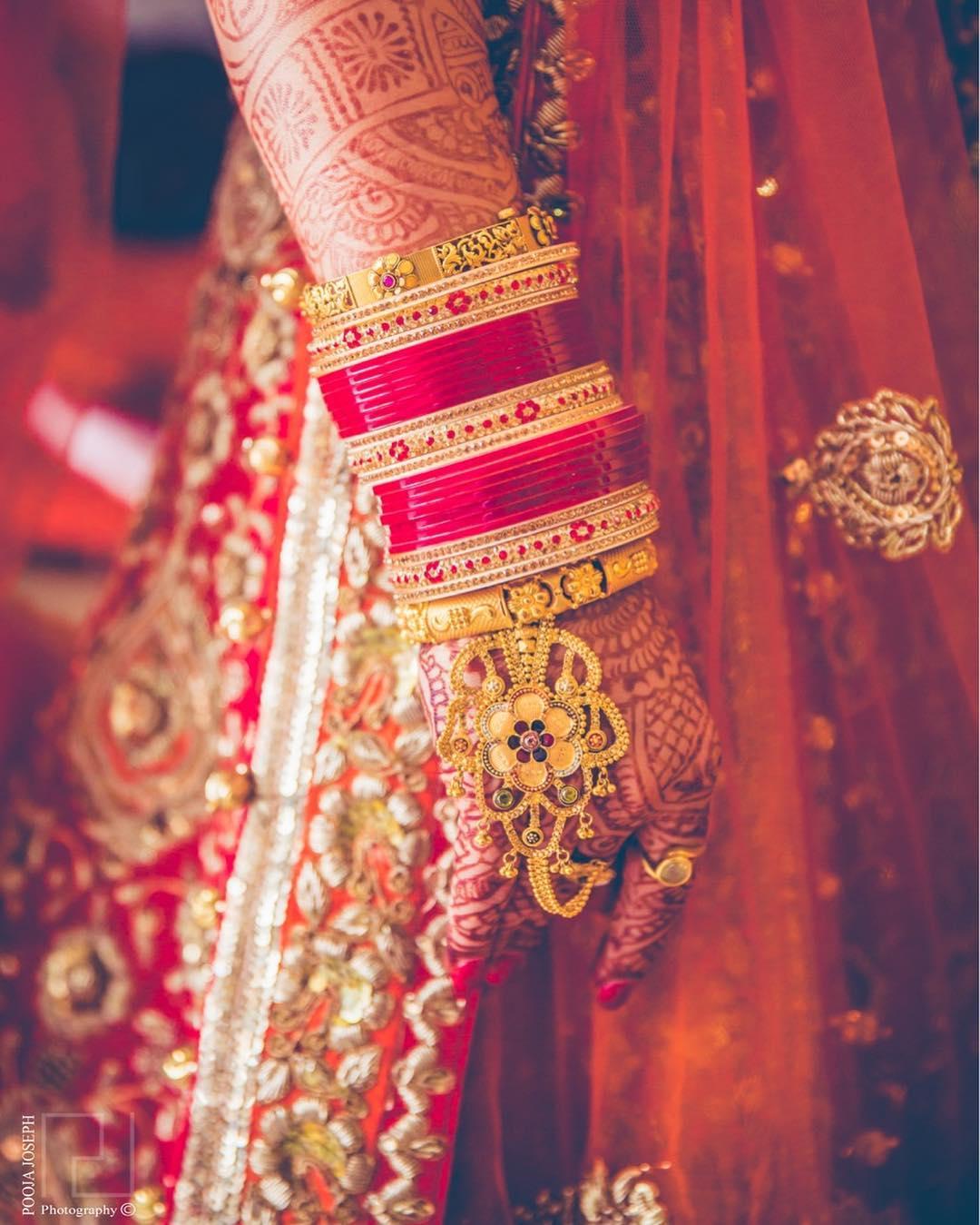 gold jewellery, chooda, gold haathphool, wedding inspiration, wedding jewellery, bride, bridal look, mehendi hands, henna hands, red lehenga, gold ring, bridal jewellery, hathphool ideas