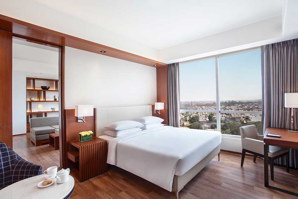 hotel room, suite room, bedroom, bed, window, curtains, coffee table, study table