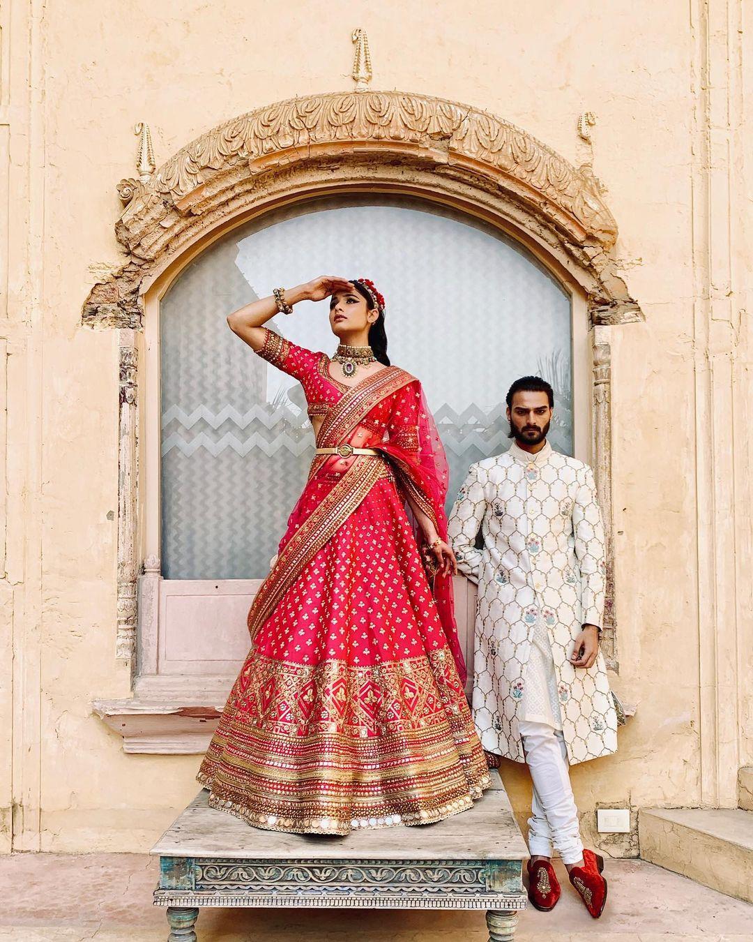 white groom sherwani & red bridal lehenga